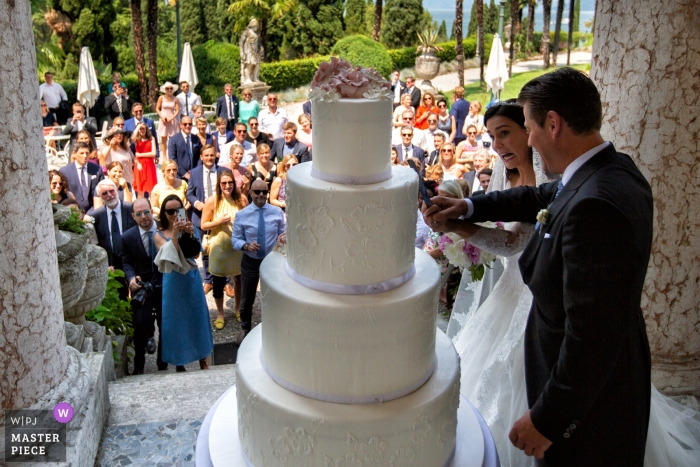 Wedding Photography from outdoors at Villa Cortine Palace Hotel - Sirmione - Lake Garda - Italy - Image of Funny cake cutting with the guests in the background