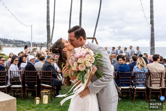 Photographie de mariage au Scripps Seaside Forum, La Jolla, Californie. Les mariés s'embrassent après la cérémonie de leur mariage.