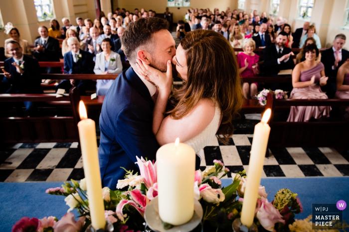 Dokumentarische Hochzeitsfotografie aus Waterville, Kerry, Irland | Erster Kuss für Braut und Bräutigam in einer vollgepackten Kirche mit Familie und Freunden