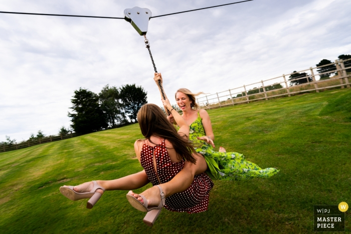 Wedding Reportage Photography at Skylark Farm, Warwickshire, UK - Image of female Guests enjoy the zipwire at the outdoor reception on the lawn.