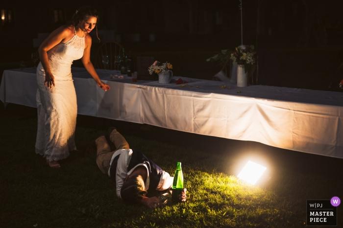 Hochzeitsfotografie - Dvorec Rakičan - Slowenien | Braut, die für den Bräutigam kommt, der draußen auf dem Gras mit Flasche liegt