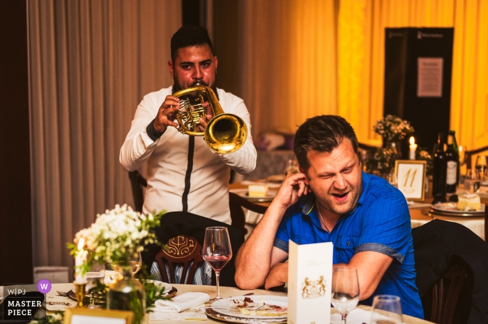 Wedding reception photography - Grand hotel Toplice, Bled, Slovenia - A guest is a party breaker - Musician with loud horn