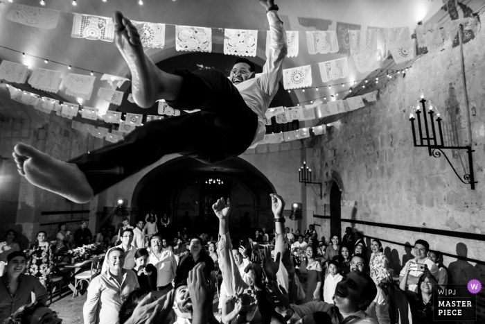 Hotel Quinta Real, Centro Histórico, Oaxaca, Mexico wedding photographer - Image of the Launching the groom into the air at the wedding reception party.