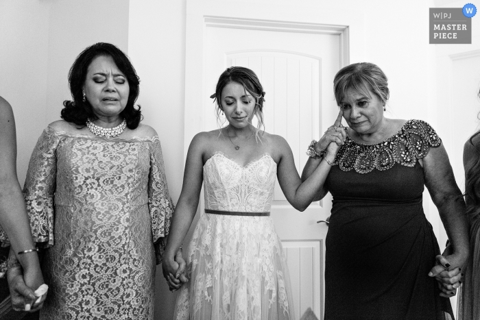 Lamoine, Maine Wedding Photography - A mother of the bride cries as she prays with her daughter and her daughter's future mother in law.
