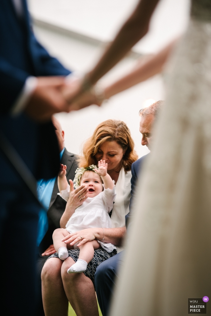 Outside ceremony venue photography - Baby is happy to see her parents during ceremony