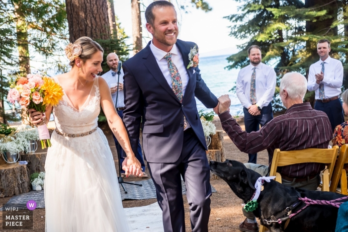 Camp Richardson Resort Lake Tahoe Wedding Venue Photographer - Bride and Groom exit as husband and wife as guests cheer them on and their dog watches them walk out
