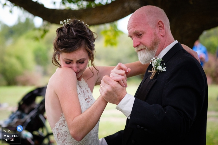 Wedding Photography from the Bride's family farm near Kalispell Montana - A bride tears up at the start of her father/daughter wedding dance.
