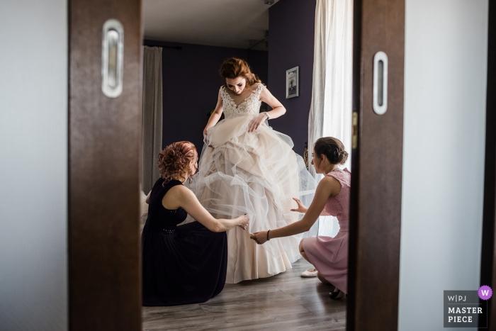 Fotografia di nozze della Bulgaria della sposa che riceve aiuto con il suo vestito prima della cerimonia