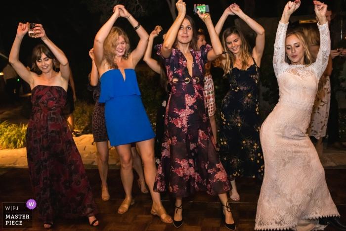 Hochzeitsfotografie vom Veranstaltungsort Adamson House, Malibu, Kalifornien - Die Braut und ihre Freunde tanzen auf der Tanzfläche.