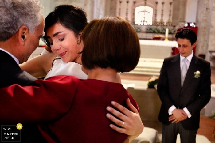 Cattedrale di Gerace, Gerace, Reggio Calabria Hochzeitsfoto - Gefühle während der Zeremonie: Braut umarmt ihre Eltern. Der Bräutigam schaut mit Gefühlen zu.
