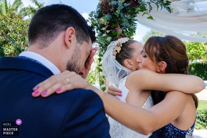 Cocentaina-Hochzeitsfoto der Braut eine Umarmung empfangend, während Bräutigam bereitsteht.