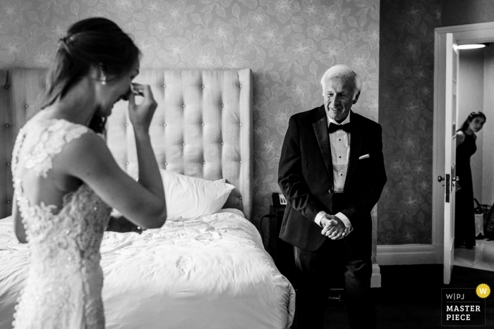 Hotel Photography during Getting Ready | Bride seeing her dad for the first time on the wedding day with her junior bridesmaid sneaking a peak.