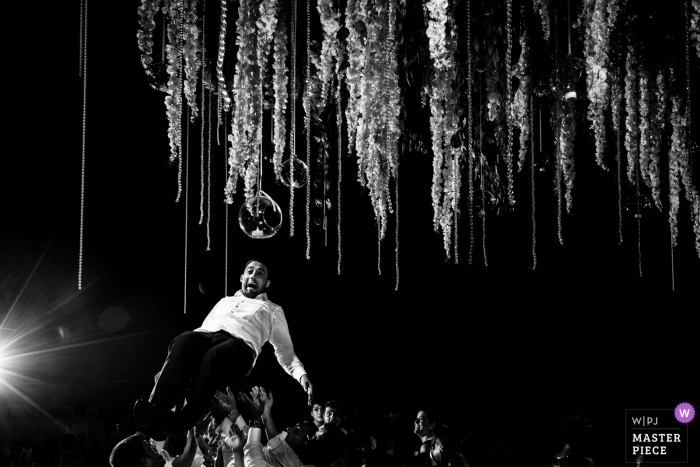 Spain Wedding Venue Photography | Groom flying on the dance floor above the guests in this black and white photo