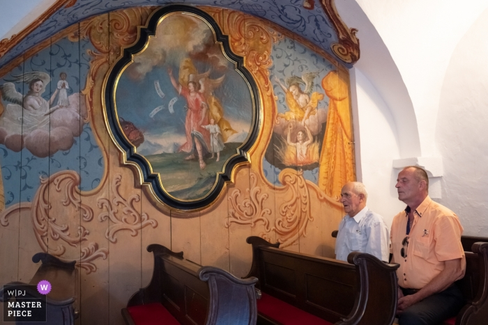 Olimije Monastary Wedding Photography - Image contains: men, pews, mural, ceremony
