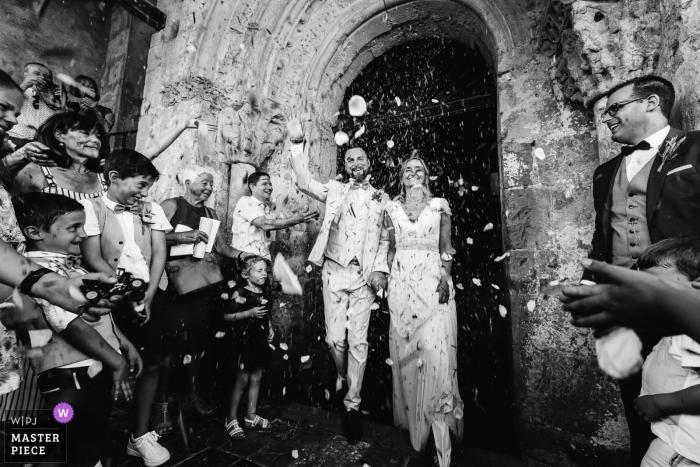 Simacourbe, Frankrijk huwelijksfotografie van de bruid en bruidegom die de kerk verlaten terwijl hun gasten hen begroeten.