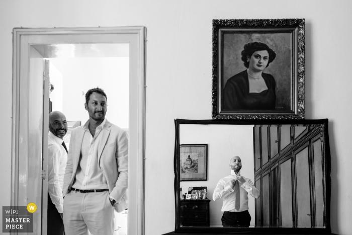 Fotografia ślubna Trapani pana młodego, szykującego się w lustrze, gdy obserwują go przyjaciele.