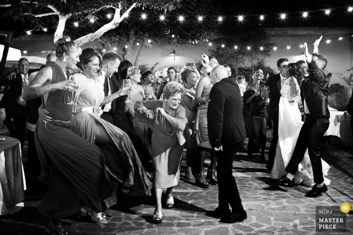 Sicily Wedding photographer takes a picture of friends of all ages as they dance happily at the wedding at Baglio Oneto in Marsala
