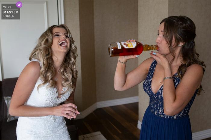 Bruidsmeisje neemt een slokje drank terwijl bruid lacht in een hotel voorafgaand aan de bruiloft in Alberta, Canada.