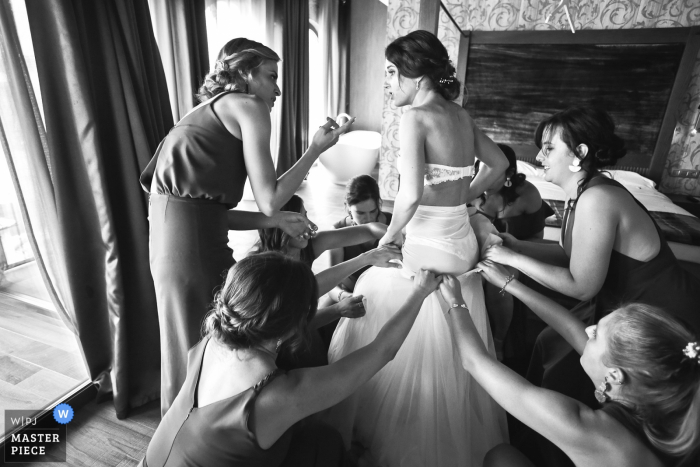 The bride is putting her dress on with help of bridesmaids - Wedding photographer from Auvergne-Rhône-Alpes
