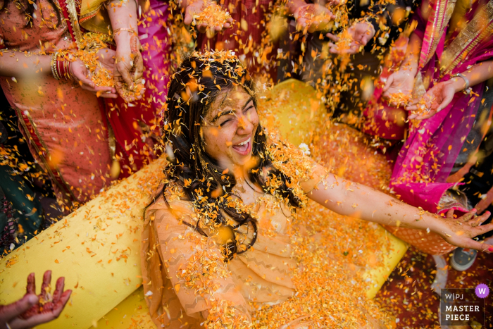 Wedding photography from bride's house in Delhi | This was a moment after the Haldi ceremony , where everyone applies turmeric paste to the bride and then showers her with flowers as a sign of affection