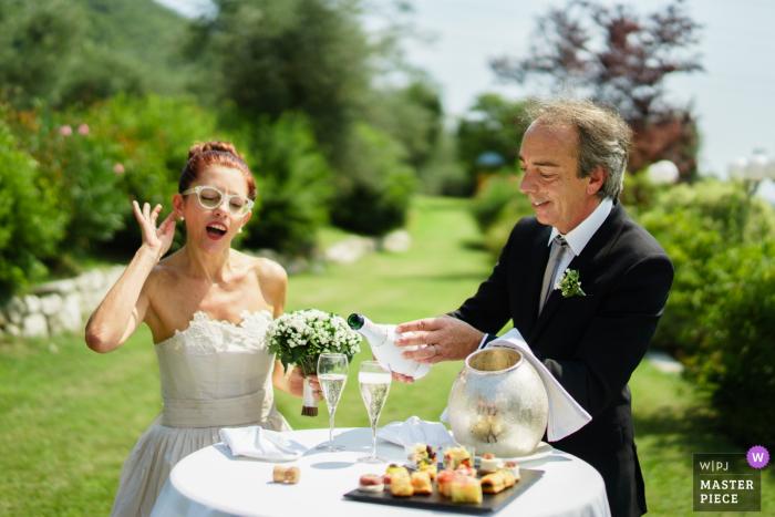 Antica Corte San Zago, Salò (Bs) - Fotógrafo de bodas - La novia se lleva la mano al oído para escuchar el coro de invitados