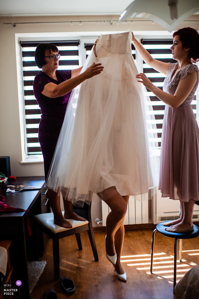 Sofia, Bulgaria wedding photograph of the bride hidden beneath her dress as she gets help.
