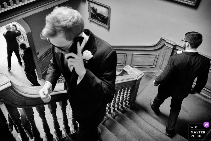 Wedding Reportage Photography from Sutton Bonington Hall, Loughborough, UK | A decisive moment on the stairs. At the bottom is the groom greeting a guest.
