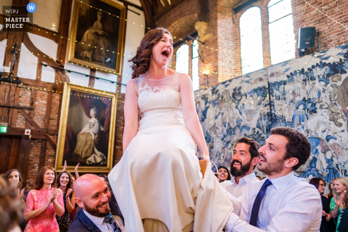Wedding Reportage Photography from the Hatfield House - Bride being lift up on the chair during dance