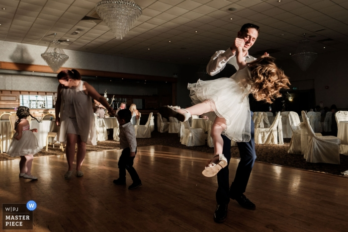 Wedding Reception venue photography: Royal Court Hotel, Portrush. - The groom swings his daughter around on the dance floor