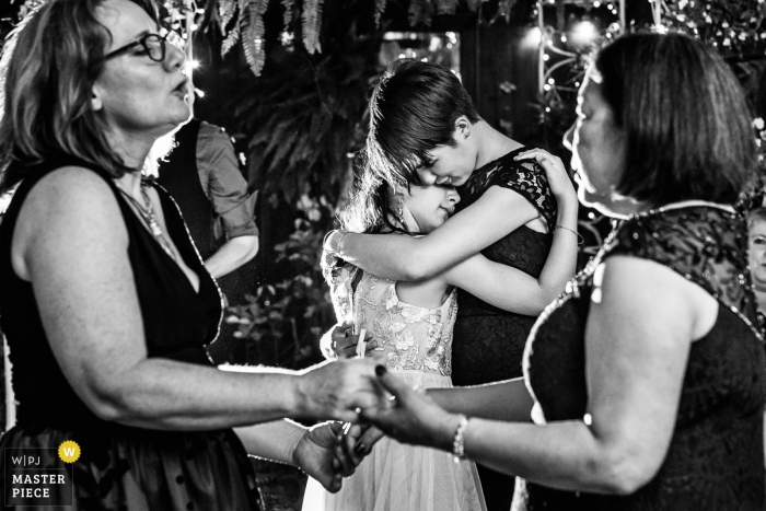 The Gables Inn, Long Beach Island, New Jersey Wedding Photography - Two young ladies hug while dancing at The Gables Inn LBI NJ