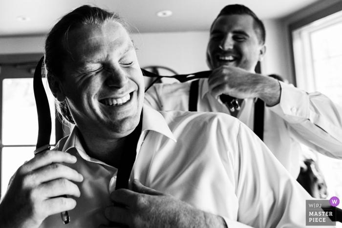 Un garçon d'honneur aide un autre garçon d'honneur à mettre ses bretelles au mariage de Bear Brook Valley NJ - New Jersey - Photojournalisme de mariage