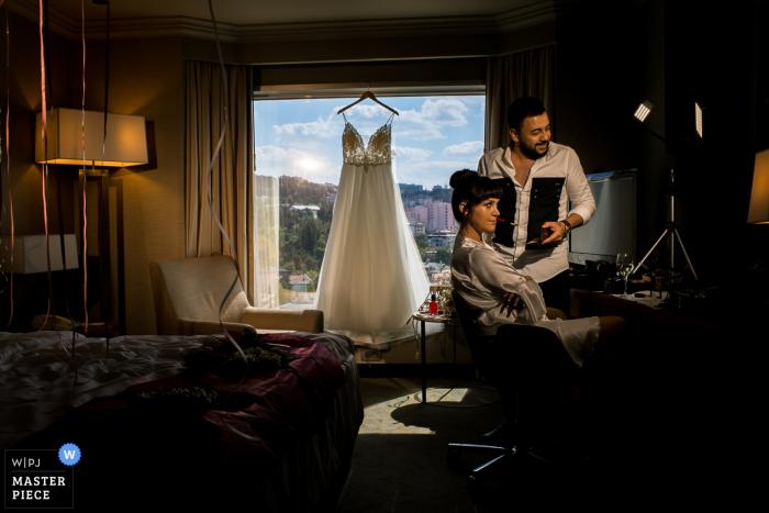 Wedding Phootgraphy from Venue - Hilton Ankara - Bride ma makijaż i suknię ślubną zawieszoną na dużym oknie z widokiem na miasto