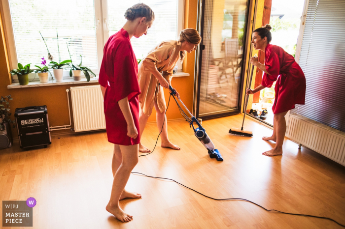 Wedding Photography at the Home of the Bride - Murska Sobota, Slovenia - Bridemaids and bride cleaning what was under the carpet