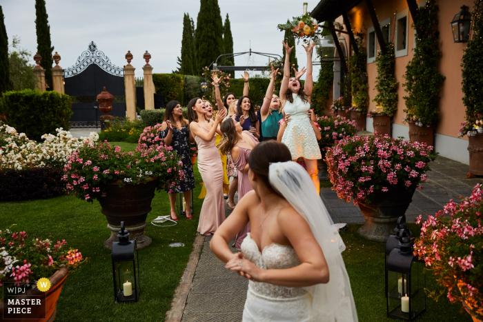 Toscana, Italia boda divertida - Foto de novia lanzando ramo a las damas de honor afuera