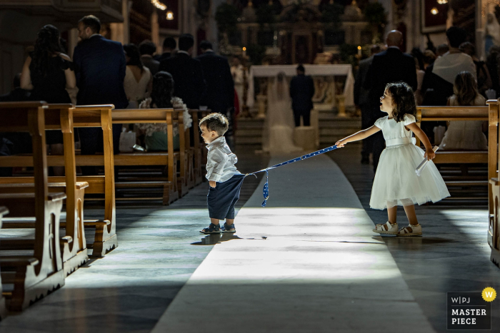 Ragusa Wedding Photography Award - children play in church during the ceremony for the bride and groom