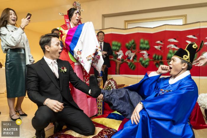 Biltmore Ballrooms Atlanta Wedding Venue Photographer - Groomsman smacking the grooms feet to test his commitment