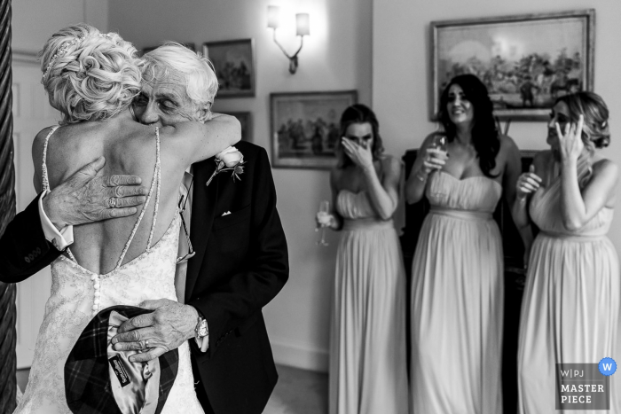 Iscoyd Park Wedding Reportage Photography - Dad hugging bride with bridesmaids in the back crying