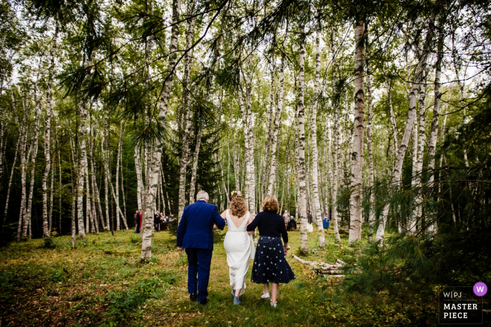 Wedding Photojournalism in Woodstock, Vermont - The bride walks toward the ceremony with her parents.