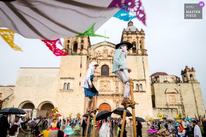 """Santo Domingo Kirche, Centro Histórico, Oaxaca, Mexiko Hochzeitsfotografie - Braut und Bräutigam feiern nach dem Verlassen der Kirche mit den """"Sancudos"""" (Stelzenläufer) der Calenda"""