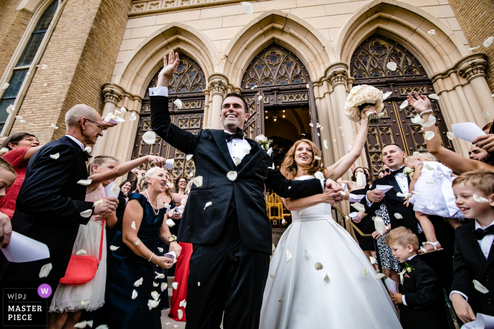 Holy Family Catholic Church - Wedding ceremony photography with bride and groom and flower petals flying