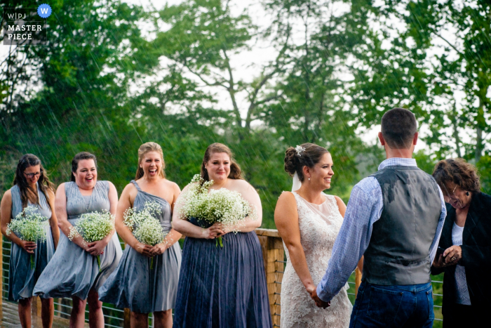 Rixey Manor, Rixeyville, VA Outdoor Wedding Venue Photos - Bridesmaids are surprised by the wind and rain during the wedding ceremony