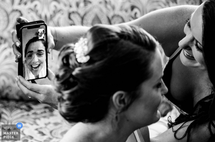 Hawthorne Hotel Wedding Photojournalism - Bride shows off her hair through FaceTime with a friend who couldn't make it to the wedding.