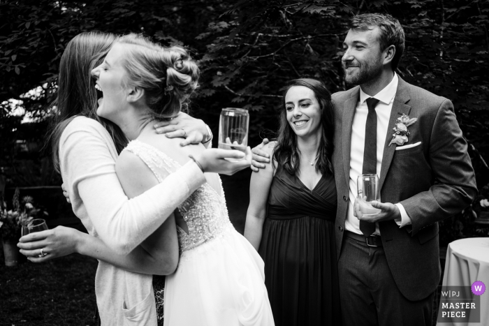 Wellspring Spa Wedding Venue Photographer - The bride and groom both hug friends at same time