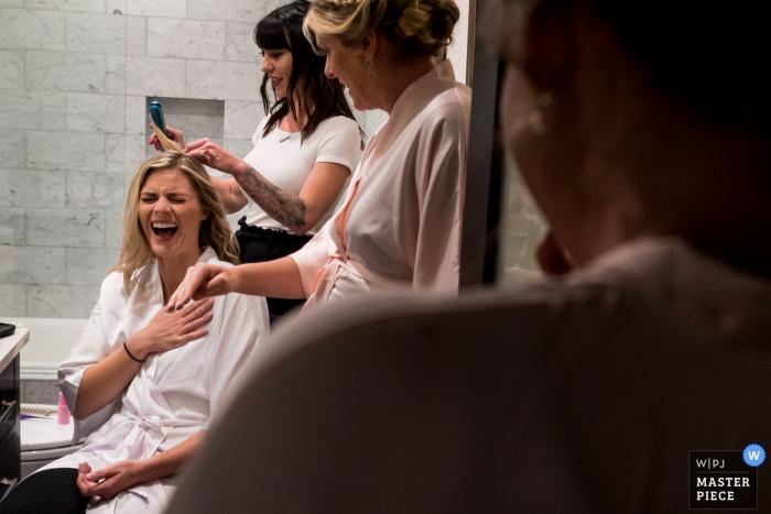 Fotografía del hotel en Colorado el día de la boda - Novia riéndose con las damas de honor durante la preparación nupcial