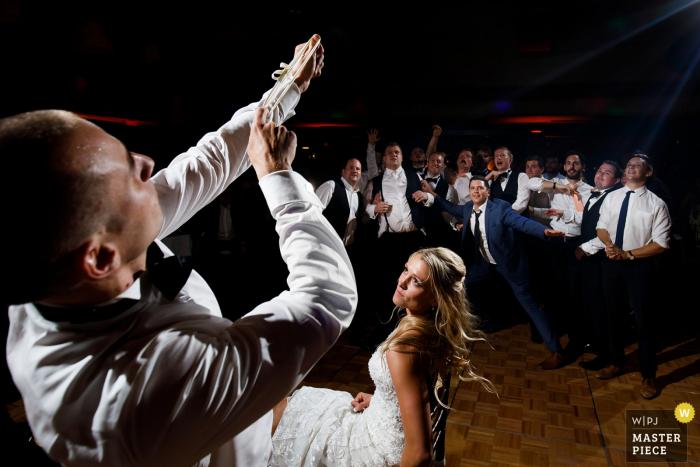 The Broadmoor Hotel, Colorado Springs, Colorado Photographe de mariage - Le marié se prépare à tirer la jarretière alors que des célibataires se bousculent pour se positionner sur la piste de danse lors d'une réception de mariage au Broadmoor.