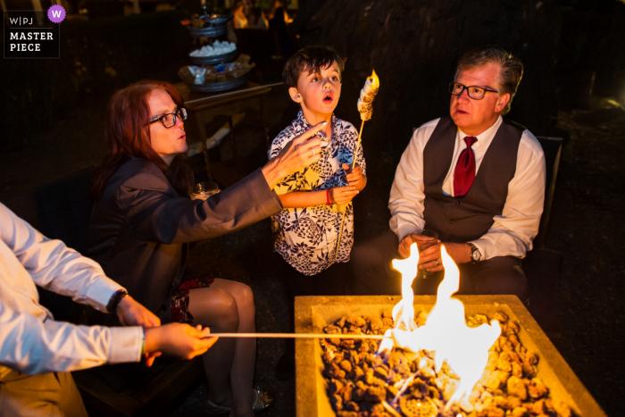 Oma, de marshmallow staat in brand! - Bruiloftreceptie fotografie 's nachts met een open vuur. - Deer Park Villa, Fairfax trouwlocatiefoto's