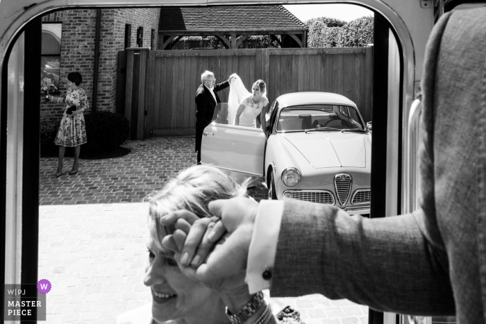 Wedding photographer for Antwerpen Flanders — bride getting out of the car with help