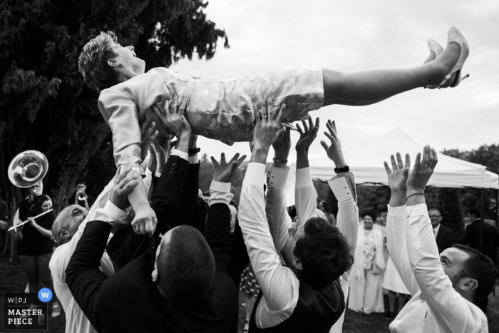 wedding photographer for Jardins d'Eyrignac   Boys are throwing the mother in law in the air