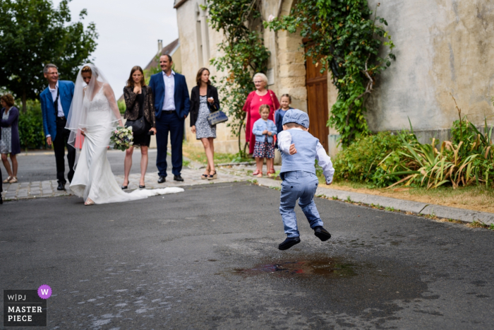 Wedding day photography from Île-de-France - Church Kid of the bride jumping in water
