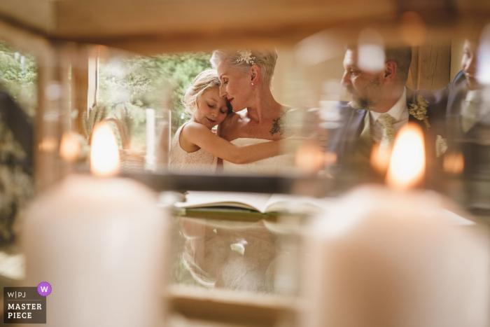 MARN BARNS Salle de mariage | La mariée et la fille partagent un câlin tandis que le marié regarde o